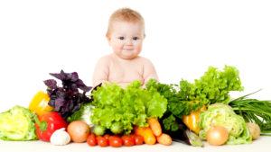 Hymyilevä vauva istuu kasvisten ympäröimänä.