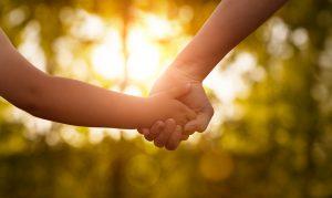 Aikuinen ja lapsi käsi kädessä, taustalla vihreä aurinkoinen maisema.