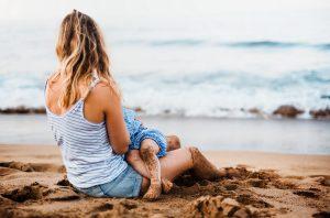 Kuvassa nainen imettää lasta yksin rannalla ja katsoo merelle.