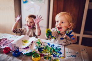 Hymyilevät lapset maalaavat sormiväreillä.