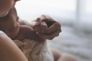 Vauva vanhemman sylissä, pitää vanhemman sormesta kiinni.