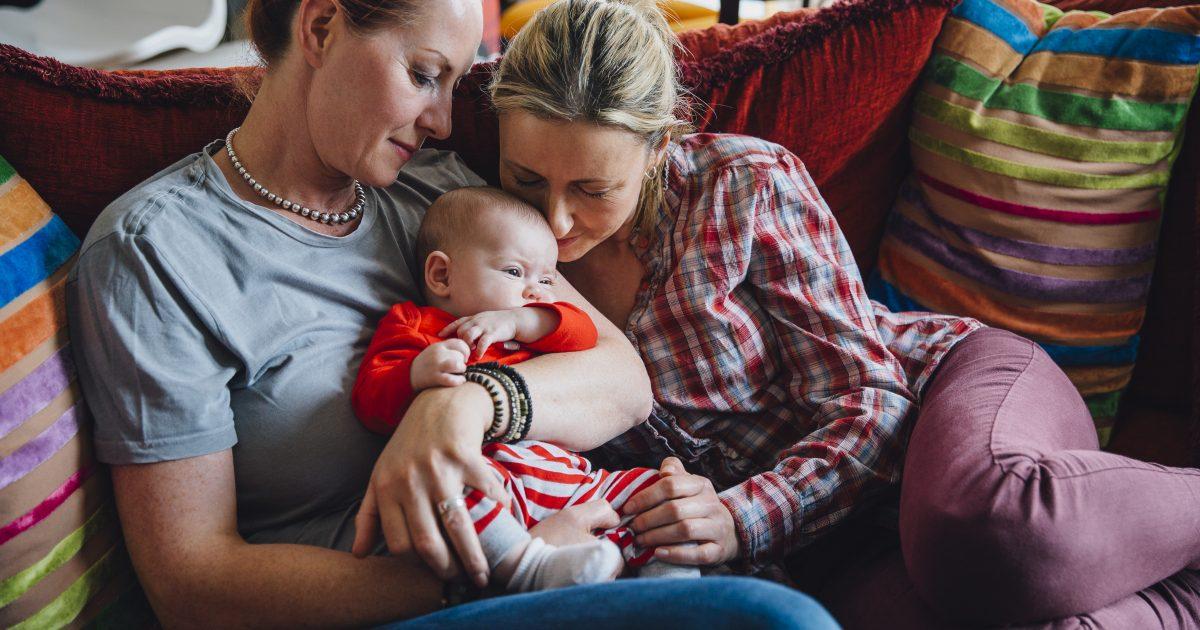 Naispari hellii pientä vauvaa punaisella sohvalla.