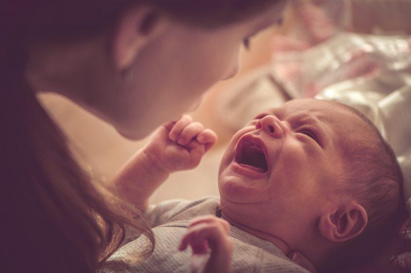 Äiti on kumartunut pienen, itkevän vauvan puoleen rauhoittelemaan häntä.
