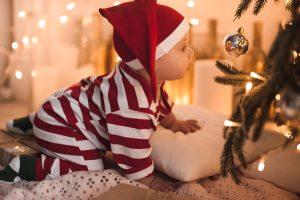 Punaraidalliseen asuun ja tonttulakkiin puettu vauva konttaa joulukuusen vieressä ja katselee joulupallosta heijastuvaa peilikuvaansa.