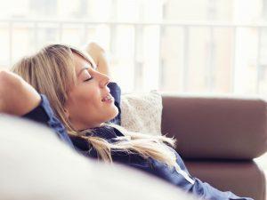 Rentoutuneen näköinen nainen lepäilee sohvalla.