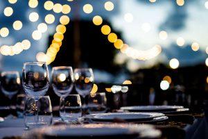Viinilaseja katettuna illallispöytään illan hämyssä, taustalla tunnelmavaloja.