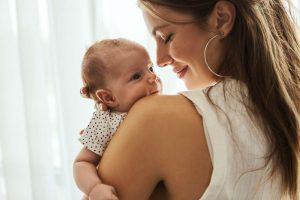 Hymyilevä äiti pitää sylissä pientä vauvaa.