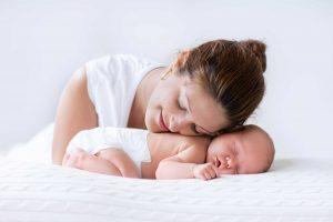 Onnellinen äiti pitää poskeaan nukkuvaa vauvaa vasten.