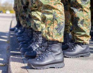 Armeijapukuisten henkilöiden jalat rivissä.