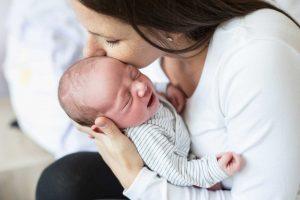 Väsynyt äiti suukottaa pientä vauvaa päälaelle.