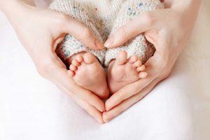 Nainen pitää vastasyntyneen vauvan varpaita käsissään niin, että käsistä muodostuu sydänmuoto. Vauvalla on päällä vaaleat villahousut.