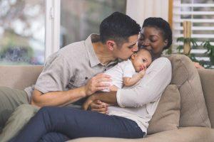 Äiti pitelee sylissä vauvaa, isä suukottaa vauvan päätä.