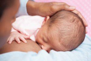 Äiti imettää unista pientä vauvaa istuen.