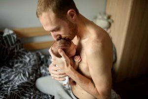 Isä pitää vastasyntynyttä vauvaa rintaansa vasten ihokontaktissa kotona makuuhuoneessa.
