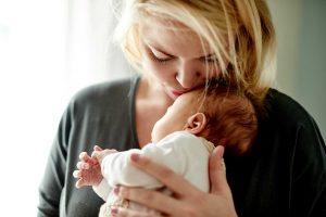 Pieni vauva sivuttain äidin sylissä, äiti suukottaa vauvan otsaa.