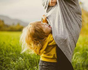 Taaperoikäinen lapsi itkee ja roikkuu äidin paidassa ulkona.